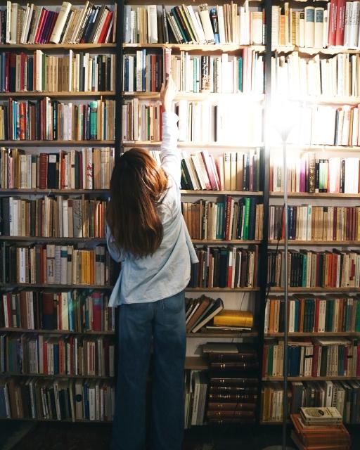 本棚に手を伸ばす少女