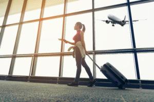 空港でトランクを引く女性と窓の外の飛行機
