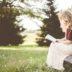 外で座って本を読む外国人女性