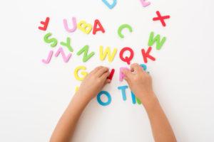 英語アルファベットのブロックを並べる子供の手