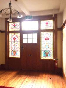 外の光が差して明るくなったおしゃれなガラス窓のある玄関