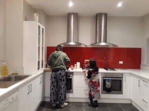 シェアハウスの白基調のキッチンで友達と料理をする宇宙さん