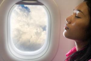 飛行機の座席で眠る女性と窓