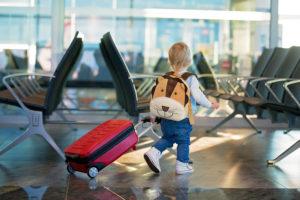 空港でキャリーケースを引っ張る小さな男の子