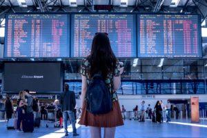 空港の電光掲示板を眺める女性