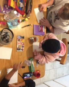 友人たちとテーブルを囲んで絵を描く様子